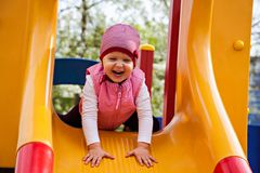 Smiling girl sitting at yellow slide Royalty Free Stock Photos