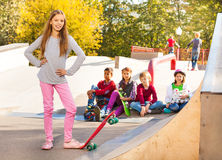 Smiling girl in with skateboard and her friends Stock Photo