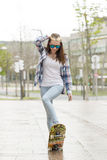Smiling girl with skateboard in the street in action. Stock Photo