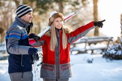 Girl on skiing shows something to his partner. Smiling girl on skiing shows something to his partner Royalty Free Stock Photos