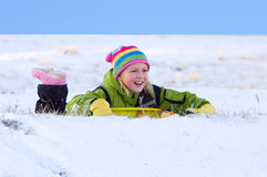 Smiling Girl Sledding. In Snow Dressed Colorfully Royalty Free Stock Photo