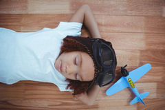 Smiling girl sleeping on the floor wearing aviator glasses and hat. With toy airplane next to her Stock Images