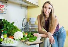 Smiling girl slicing green pepper Stock Images