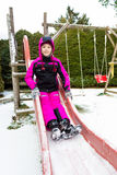 Smiling girl on slide at cold snowy day Stock Image