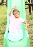 Smiling girl on a slide Royalty Free Stock Images
