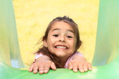 Smiling girl on a slide Stock Photography