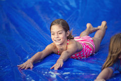 Smiling girl sliding down an outdoor slip and slide Royalty Free Stock Photos