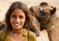 The smiling girl. A small girl is smiling looking at the camera with a camel in her background in the pushkar camel fair ground Stock Photo