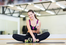 Smiling girl with smartphone and earphones in gym Stock Photo