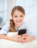 Smiling girl with smartphone at home Royalty Free Stock Photos