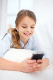 Smiling girl with smartphone at home Stock Images