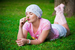 Smiling girl smelling flower. On the grass royalty free stock photo