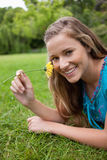 Smiling girl smelling a yellow flower while lying Royalty Free Stock Images
