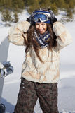 Smiling girl with snow on her face and hair. Young beautiful girl standing with snow on her face, hair and smiling, sunny winter day Royalty Free Stock Image