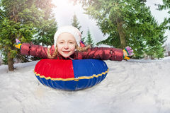 Smiling girl on snow tube in winter during day Stock Images
