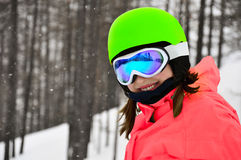 Smiling girl in snowboard glasses. Active smiling girl in snowboard glasses and helmet in winter forest Stock Photography