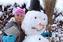 Smiling girl with snowman Royalty Free Stock Images