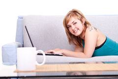 Smiling girl on sofa with laptop Stock Image