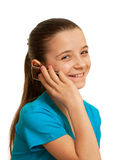 Smiling girl speaking on the mobile phone. A pretty girl in blue is holding a mobile phone in her hand; isolated on the white background Royalty Free Stock Images