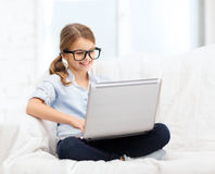 Smiling girl in specs with laptop computer at home. Home, leisure, technology and internet concept - little student girl in eyeglasses with laptop computer at Royalty Free Stock Photography