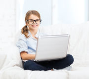 Smiling girl in specs with laptop computer at home. Home, leisure, technology and internet concept - little student girl in eyeglasses with laptop computer at Stock Images