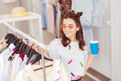 Smiling girl spending her leisure time in shopping mall. Leisure time. Smiling appealing girl spending her leisure time in shopping mall while drinking coffee royalty free stock photo