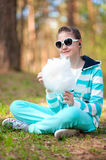 Smiling girl in sportswear with cotton candy in su Stock Photography