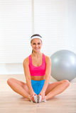 Smiling girl in sportswear sitting in yoga pose Royalty Free Stock Images