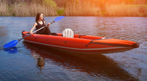 The smiling girl -the sportswoman with long,dark hair in black,sportswear rows with an oar on the lake in a red, inflatable canoe Royalty Free Stock Photography