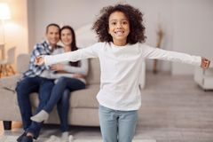 Smiling girl spreading her arms. My best parents. Pretty cheerful curly-haired girl smiling and spreading her arms and her sitting on the couch in the background Royalty Free Stock Photo