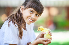 Smiling girl with a spring duckling Royalty Free Stock Photos