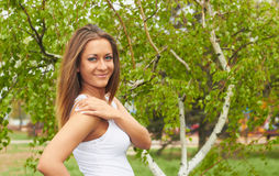 Smiling girl on a spring morning. Young girl in a white T-shirt against the spring birch Stock Photo