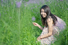 Smiling girl squatting on the lavender lens Royalty Free Stock Photo