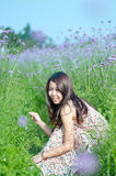 Smiling girl squatting on the lavender lens Royalty Free Stock Images