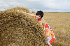 Smiling girl at a stack of straw Stock Photos