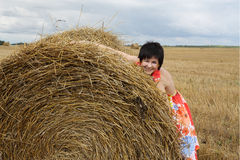 Smiling girl at a stack of straw Royalty Free Stock Photography
