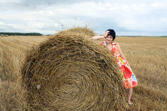 Smiling girl at a stack of straw Royalty Free Stock Image