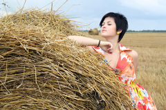 Smiling girl at a stack of straw Royalty Free Stock Photos