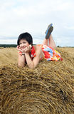 Smiling girl on a stack of straw Stock Images