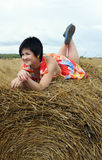 Smiling girl at a stack of straw Stock Images