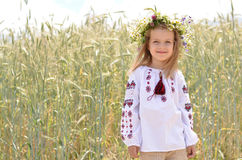 Smiling girl standing against wheat field background Royalty Free Stock Photos