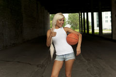 Smiling girl standing with basketball, thumbs up Stock Photo