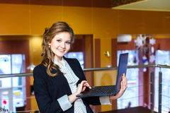 Smiling girl standing in a cafe and working on laptop Royalty Free Stock Images