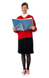 Smiling girl standing with exercise book Stock Photos