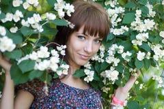 Smiling girl standing among flowers Stock Photo