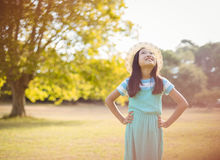 Smiling girl standing with hand on hip in park. On a sunny day Royalty Free Stock Photos