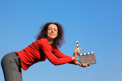 Smiling girl standing in hands clapperboard Royalty Free Stock Photography