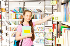 Smiling girl standing among library shelves. And holding a book Royalty Free Stock Photography