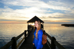 Smiling girl standing on pier on hiking trip. Royalty Free Stock Photos