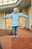 Smiling girl standing on stone curb Stock Photo